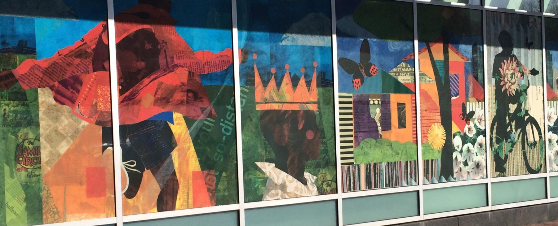 A window mural of Black folks thriving: riding bikes, running through the streets, wearing a crown.