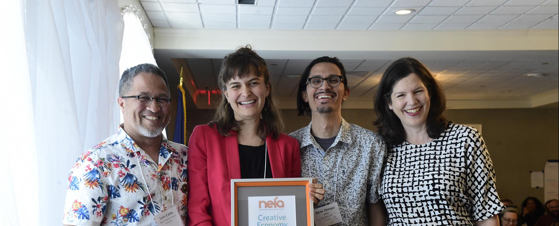 "Four people smile and pose. One of them holds a framed certificate that reads ""Creative Economy Award."""