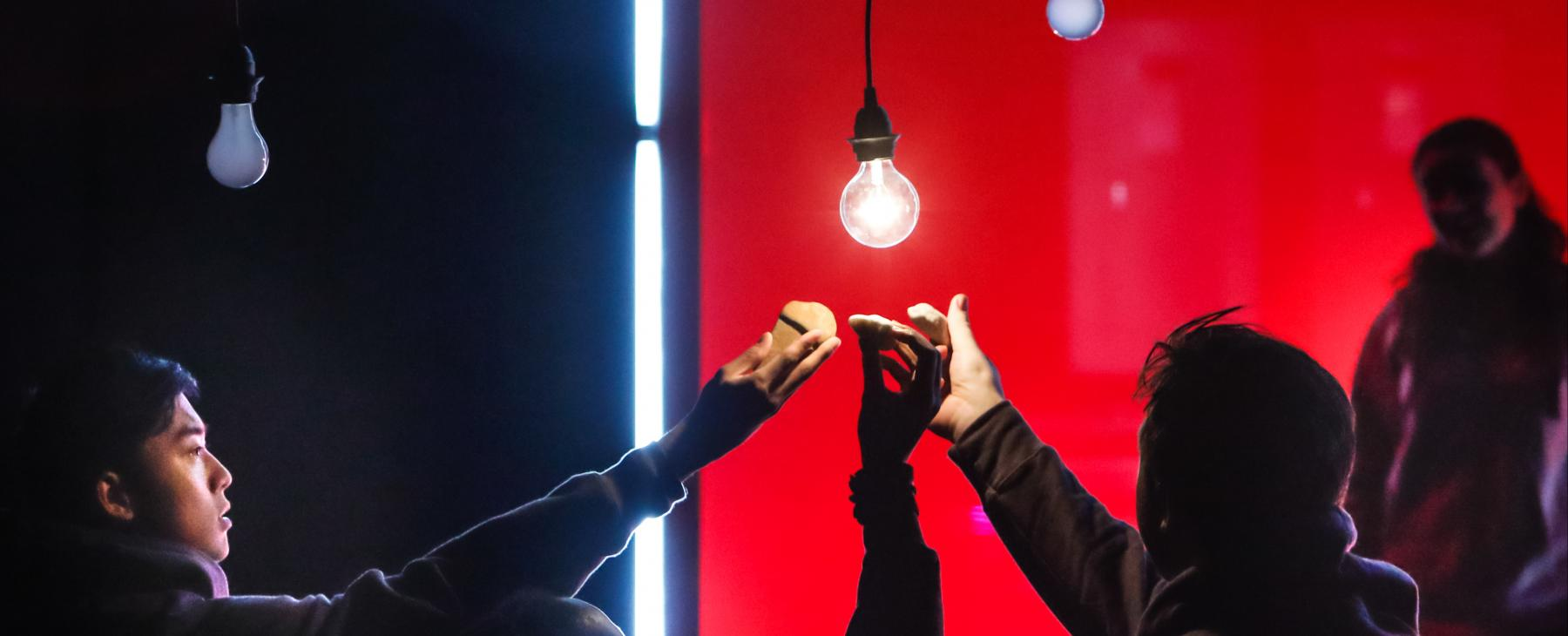 A group of dramatically lit performers all reach toward one lit light bulb, hanging on a wire from the ceiling.