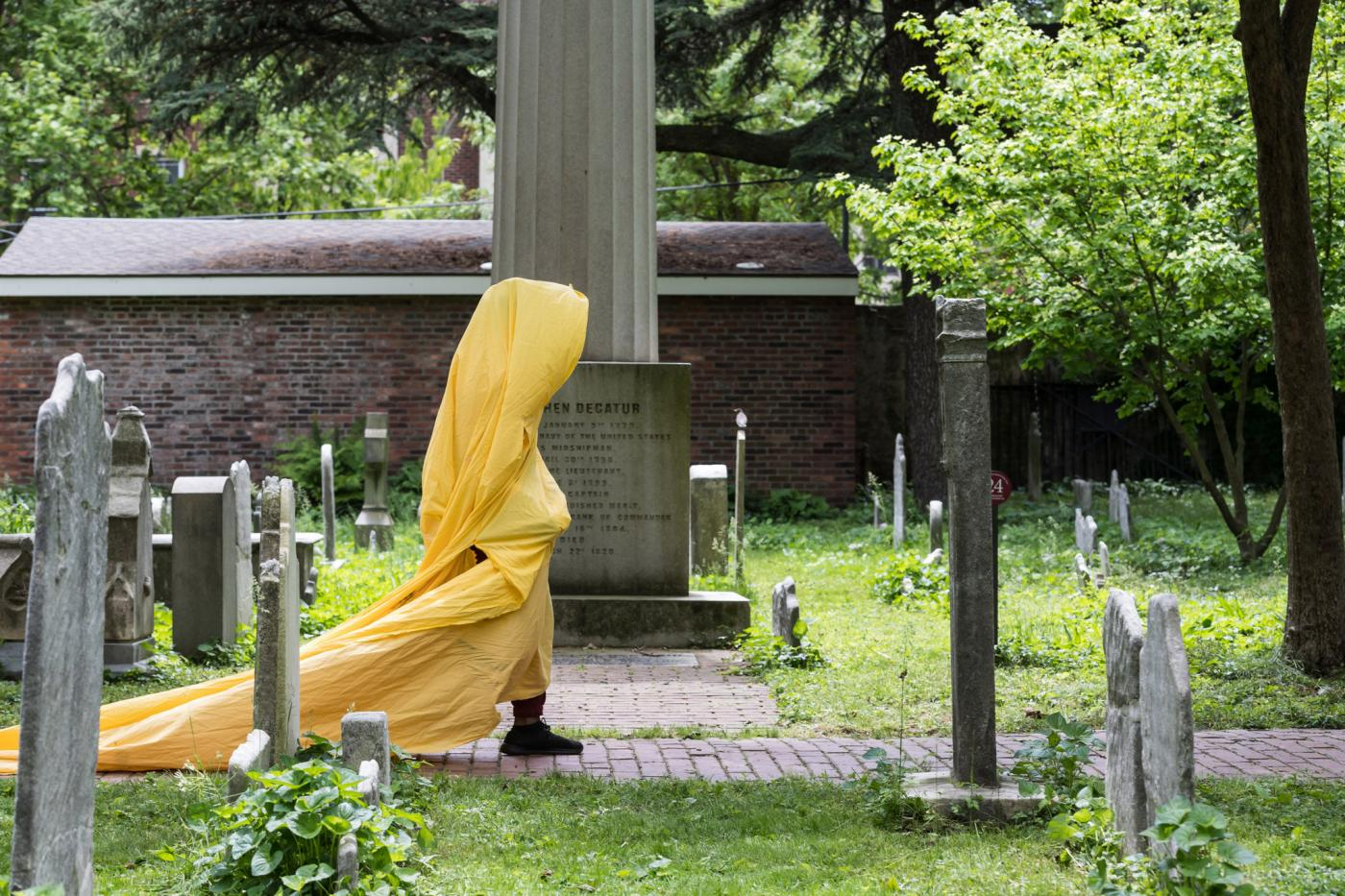A person, wrapped in a yellow tarp, walks through a graveyard.