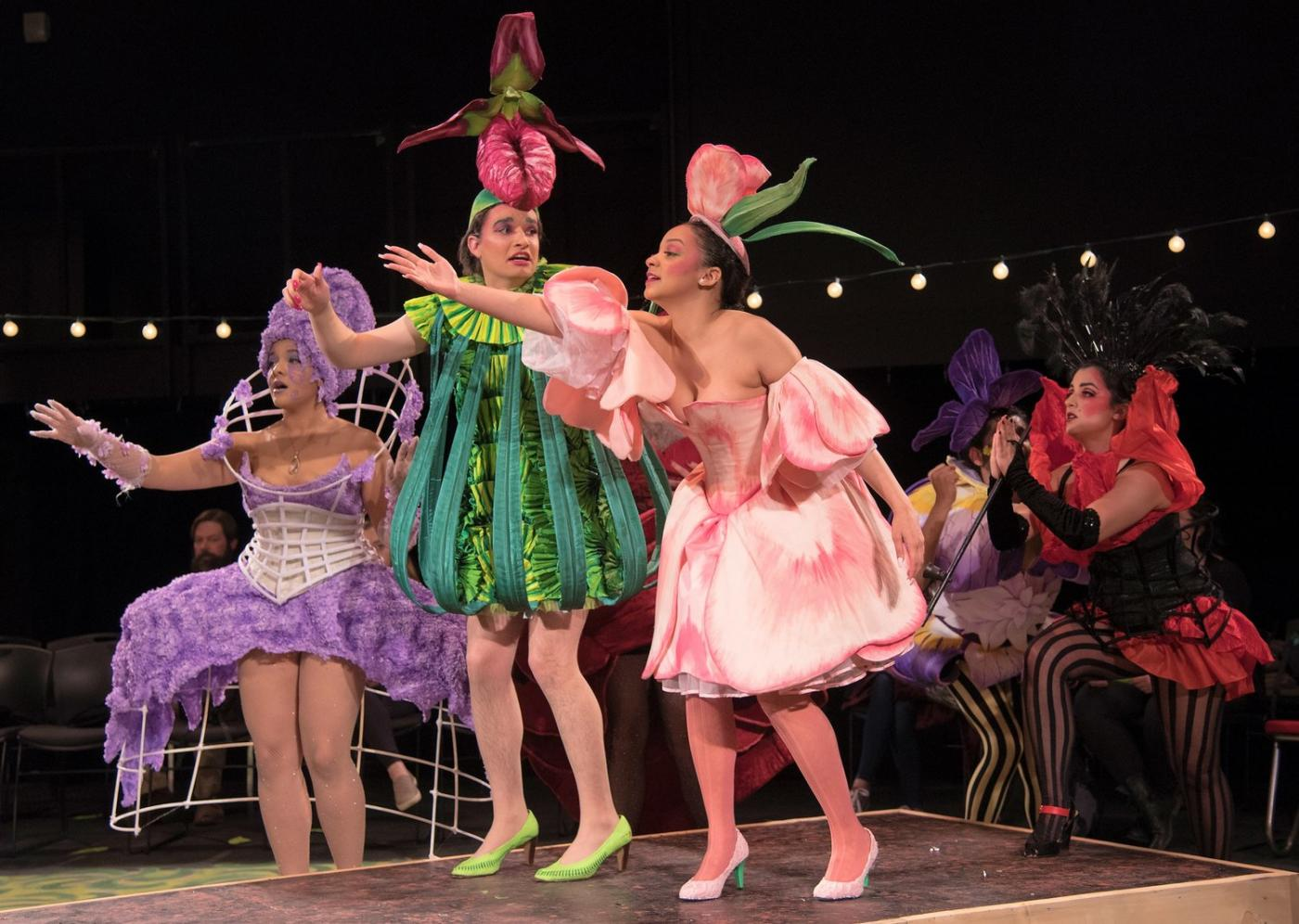 On a stage, four women in purple, pink, and green flower costumes perform.