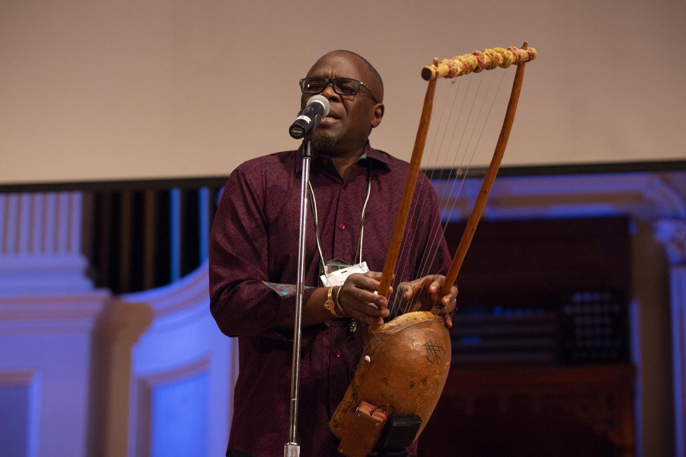 artist Samite Mulondo plays a litungu, a seven stringed instrument, and sings into a standing mic at the 2018 Idea Swap on the Great Hall stage at Mechanics Hall. Samite's eyes are closed as he performs. Blue lighting on the stage and a blank projector screen are seen in the background.