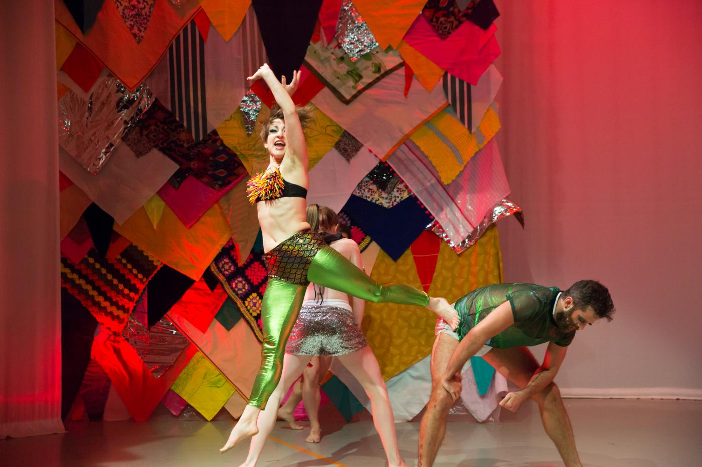Four dancers, in green, gold, fishnet, shiny fabrics, dance in front of a quilted backdrop.