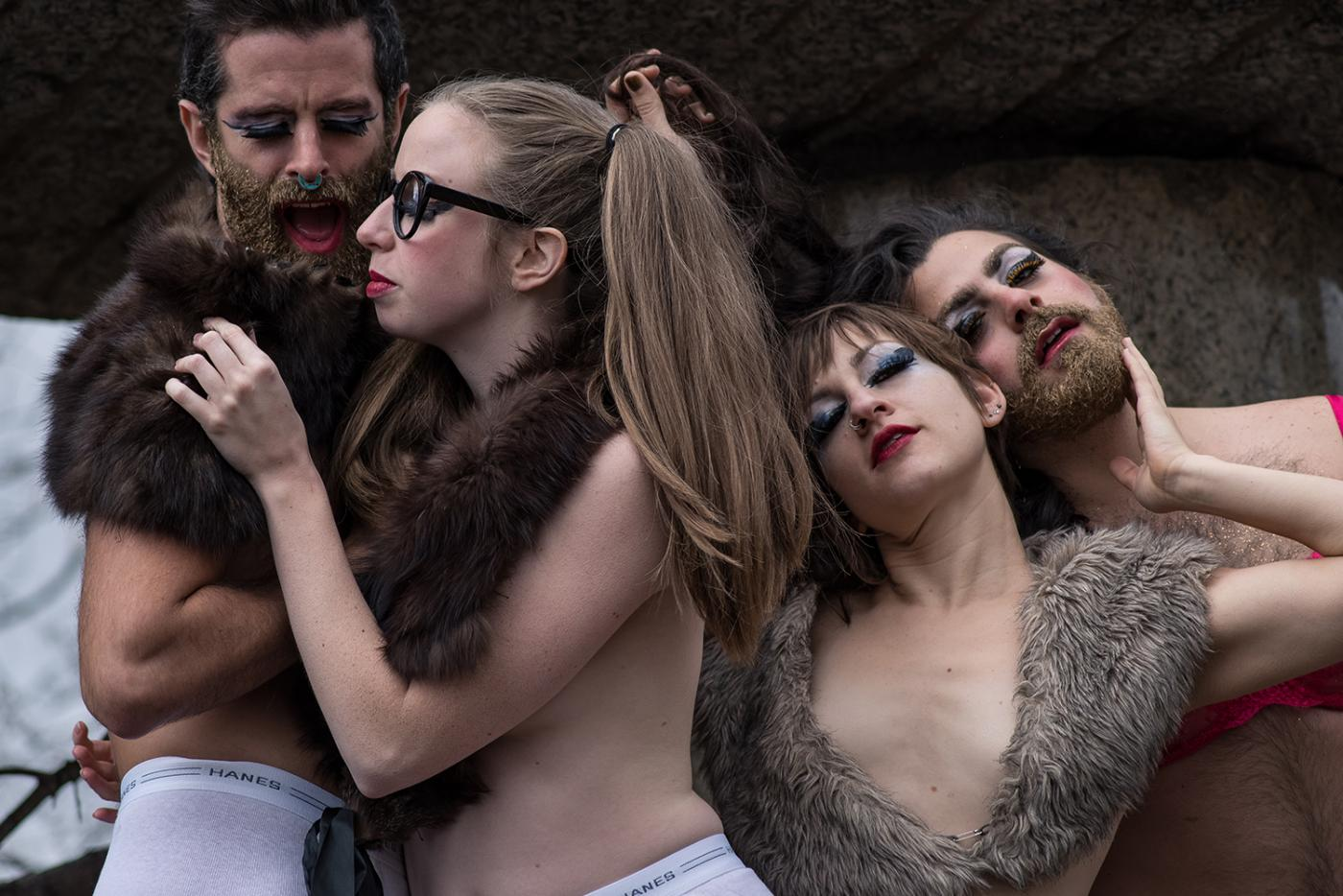 Four dancers, in mens briefs and fur shawls, caress each other.