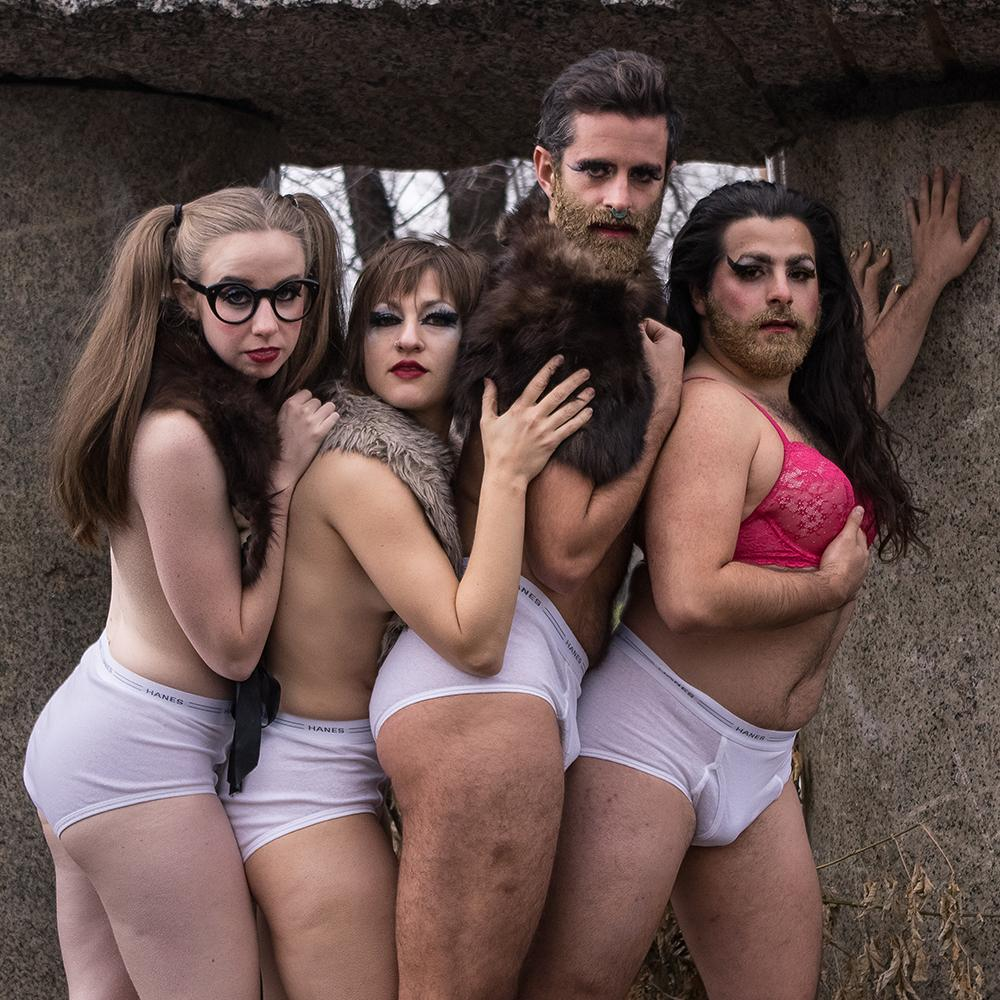 Four dancers, in mens briefs and fur shawls, pose.