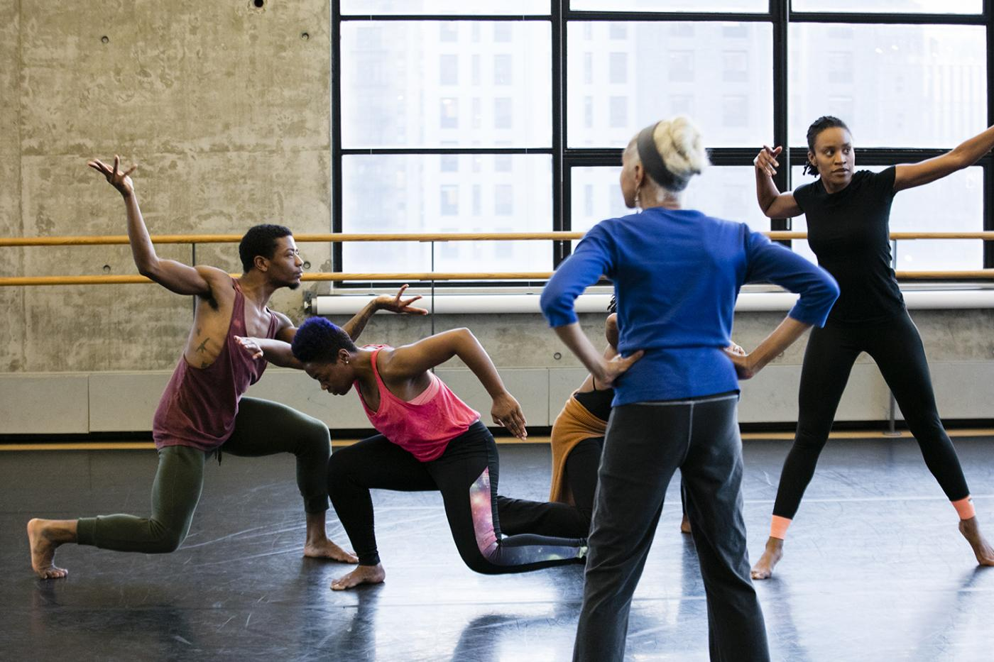 In a dance studio, four black dancers move in sweats.