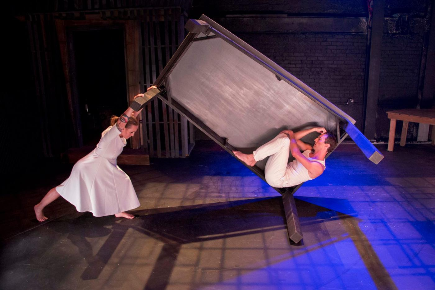 Dancer in a dress holds up one side of a sideways box containing a crouching dancer in pants.