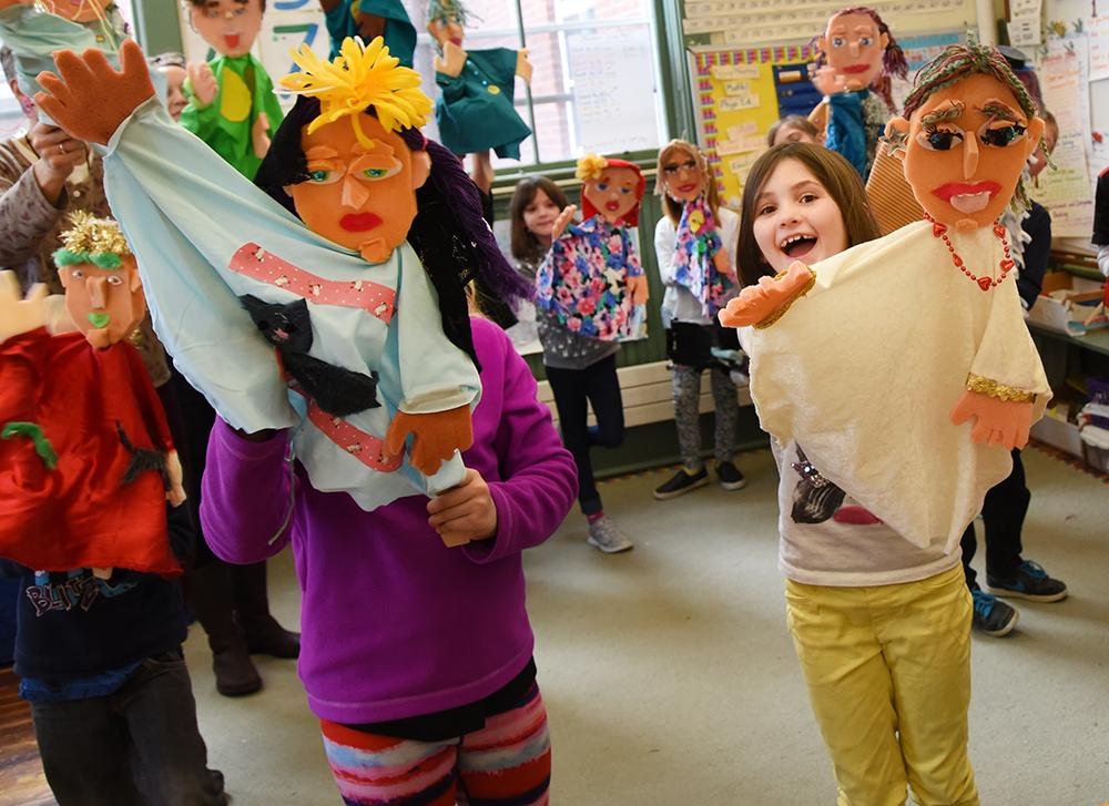 A group of colorfully dressed children pose with the large cloth puppets they made in their images.