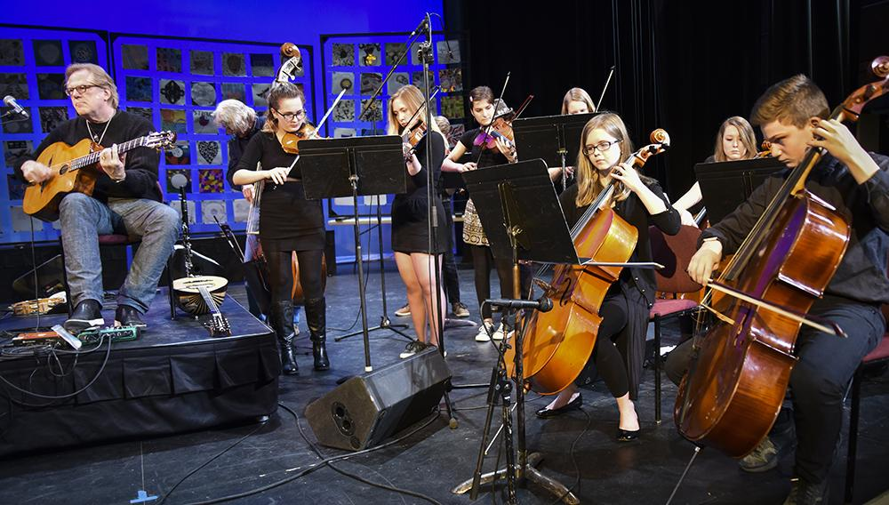 A large group of musicians of all ages play a variety of stringed instruments onstage in a black box theater.