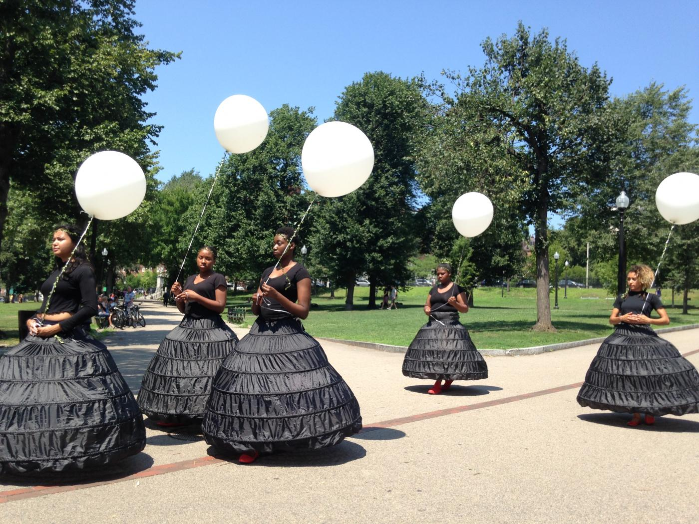 Five women of color in black dresses, holding white balloons by white ribbons, walk through a park.