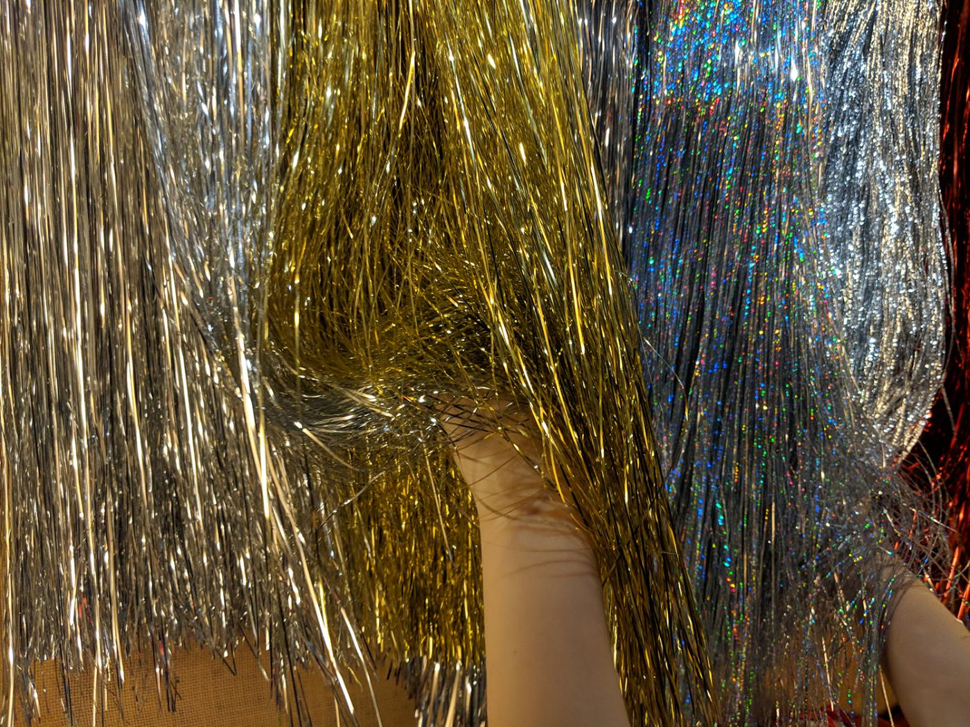 Hands rustle through gold and silver tinsel hanging on wall.