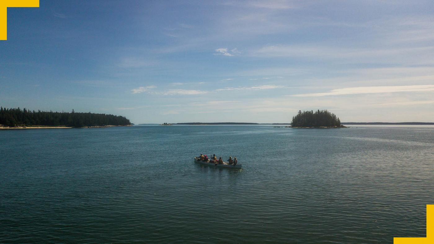 From the coast, ten canoers on a canoe make their way through the isles of Maine.