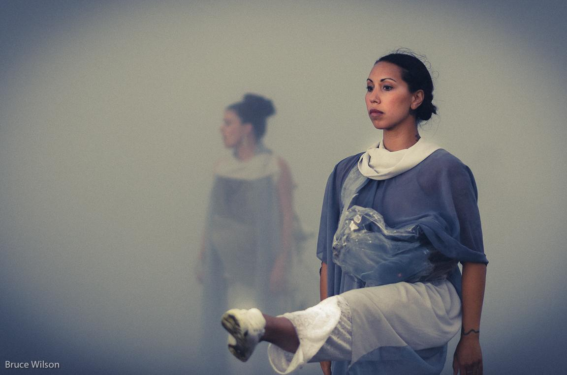 A dancer lifts her leg, staring straight ahead, while another dancer deeper in the fog is less visible