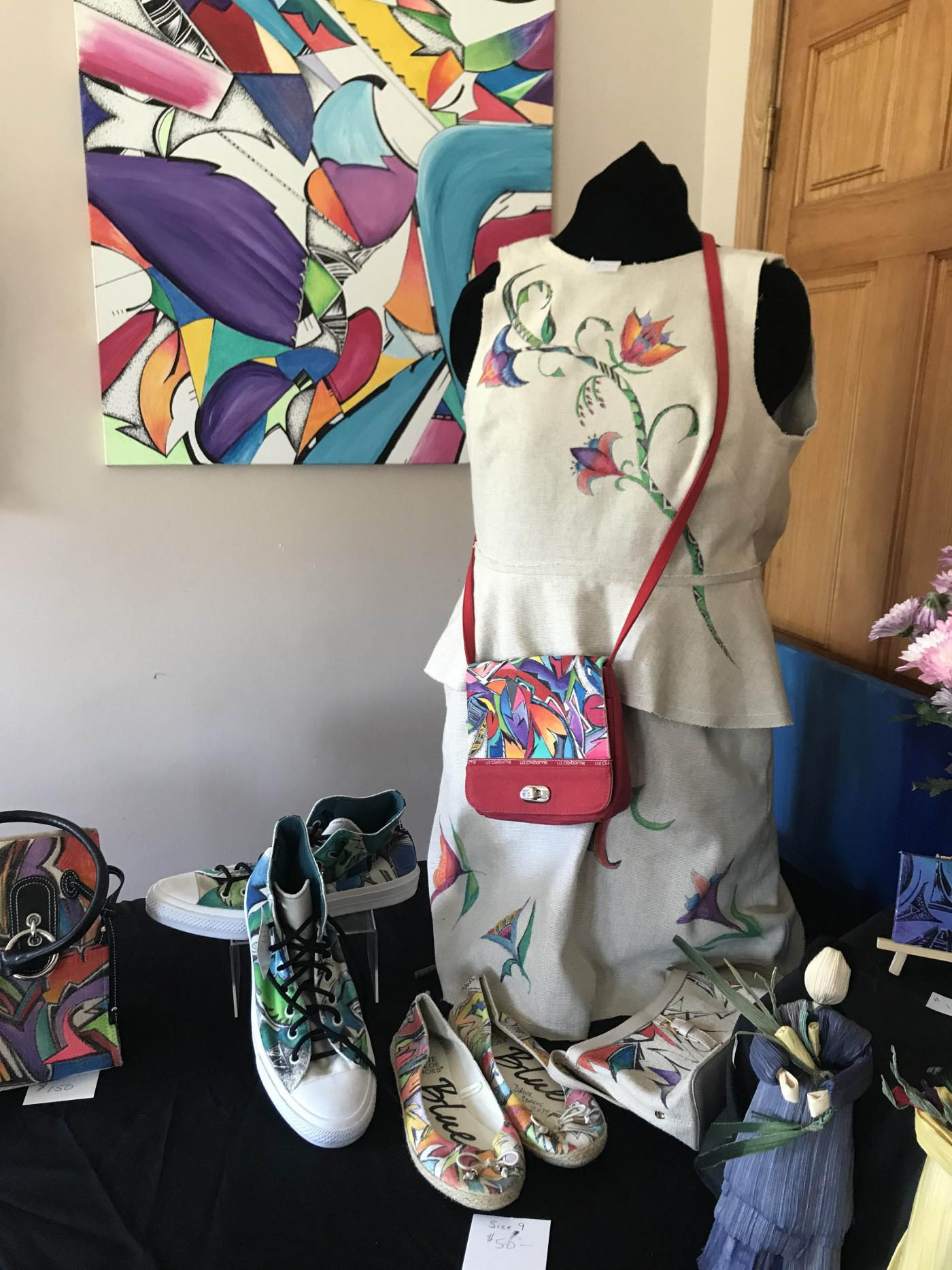 Display of artwork in a studio; colorful, graphic designs on canvas as well as a dress form, purse, and sneakers.