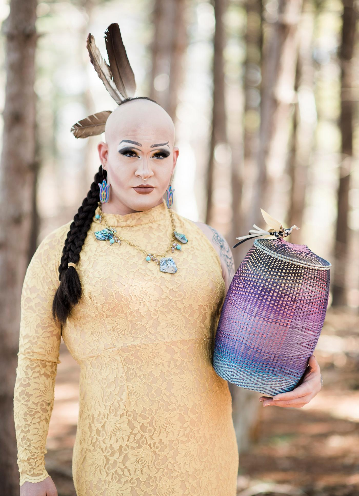 A person wearing a yellow dress and with Native American regalia and holding a multi-colored woven basket stands in a forest on a sunny day