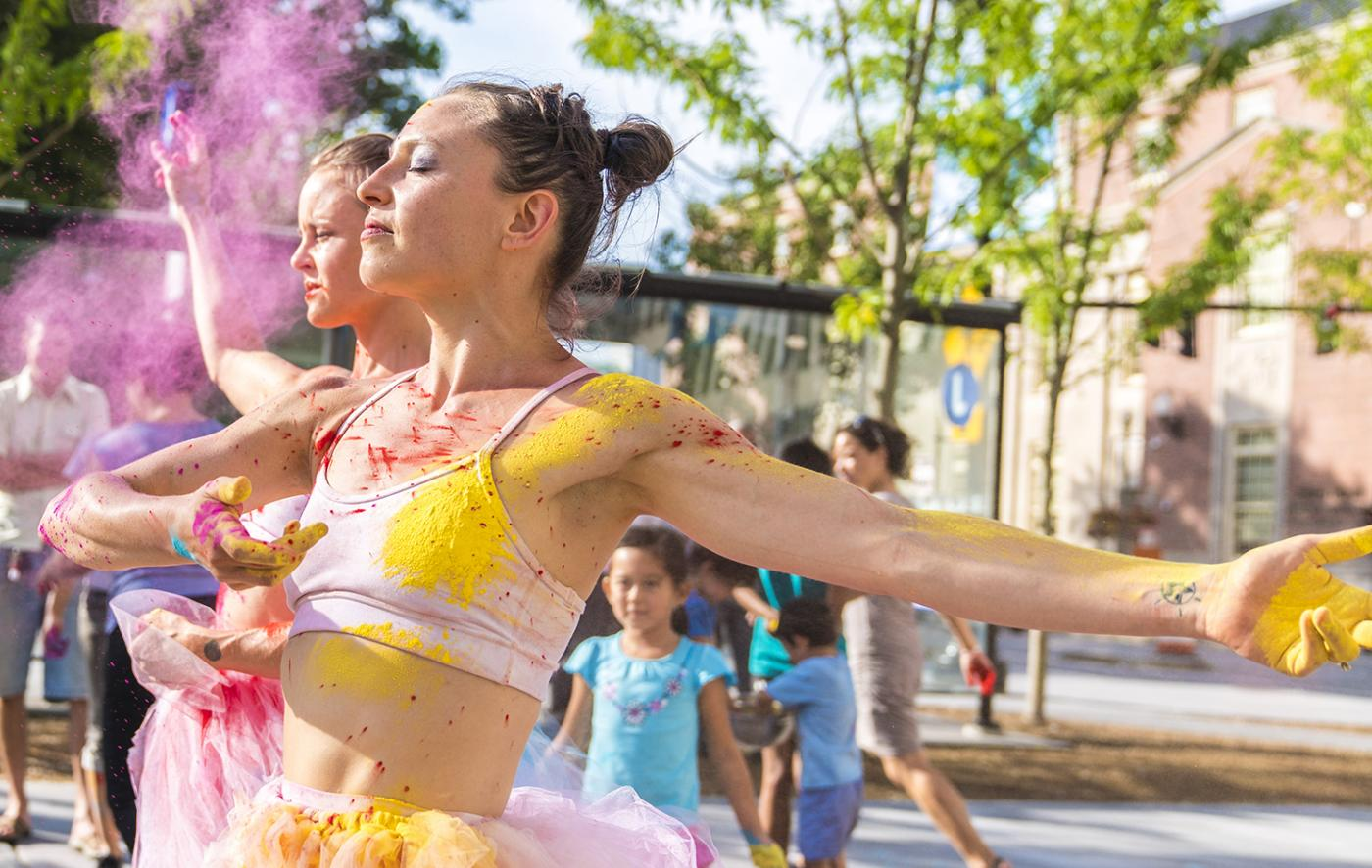 A dancer, in a tutu, on a city street, poses in color burst powder.