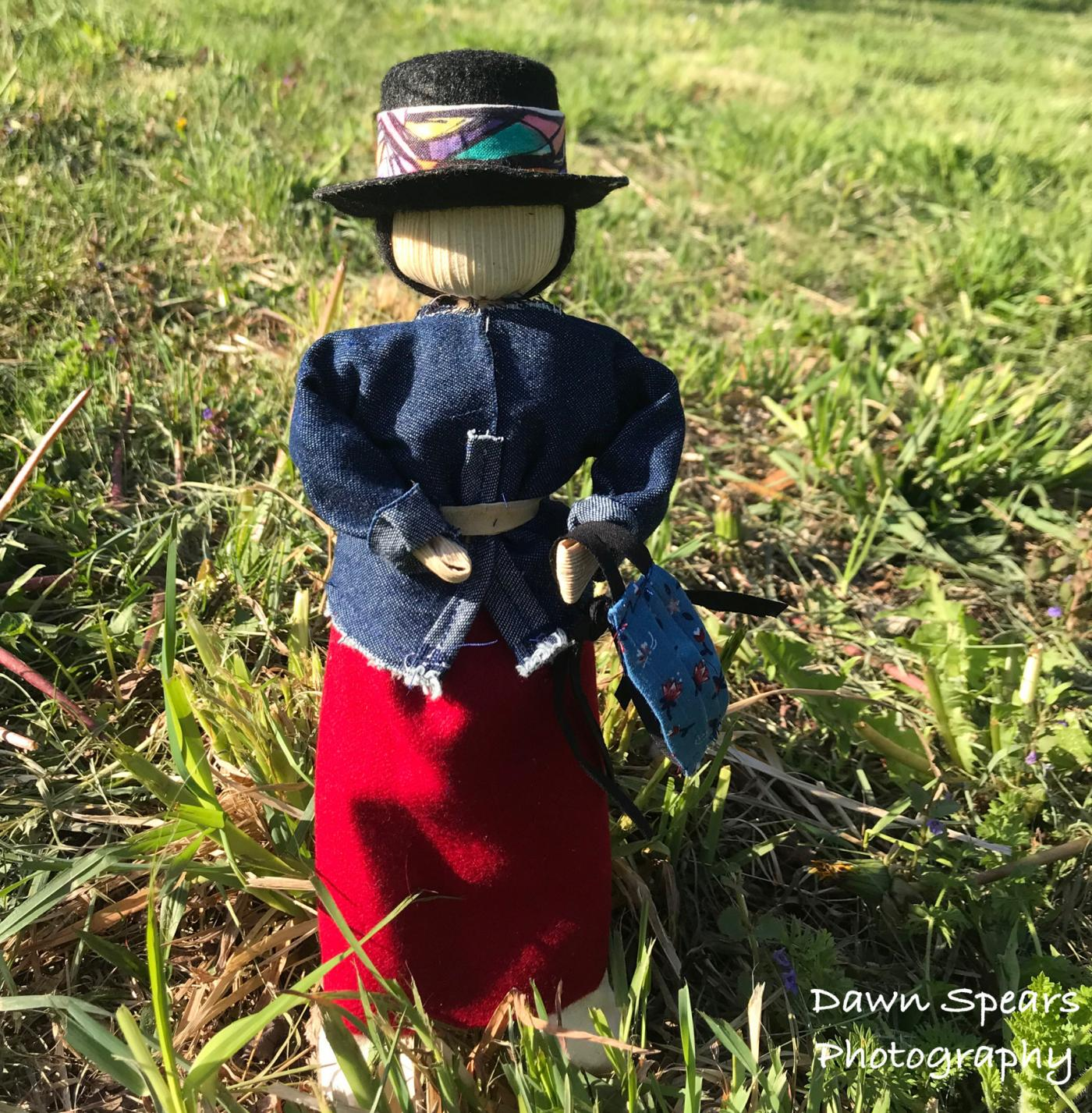 Corn husk doll dressed in black hat with colorful band, denim belted top, and long red skirt, standing on a sunny lawn.