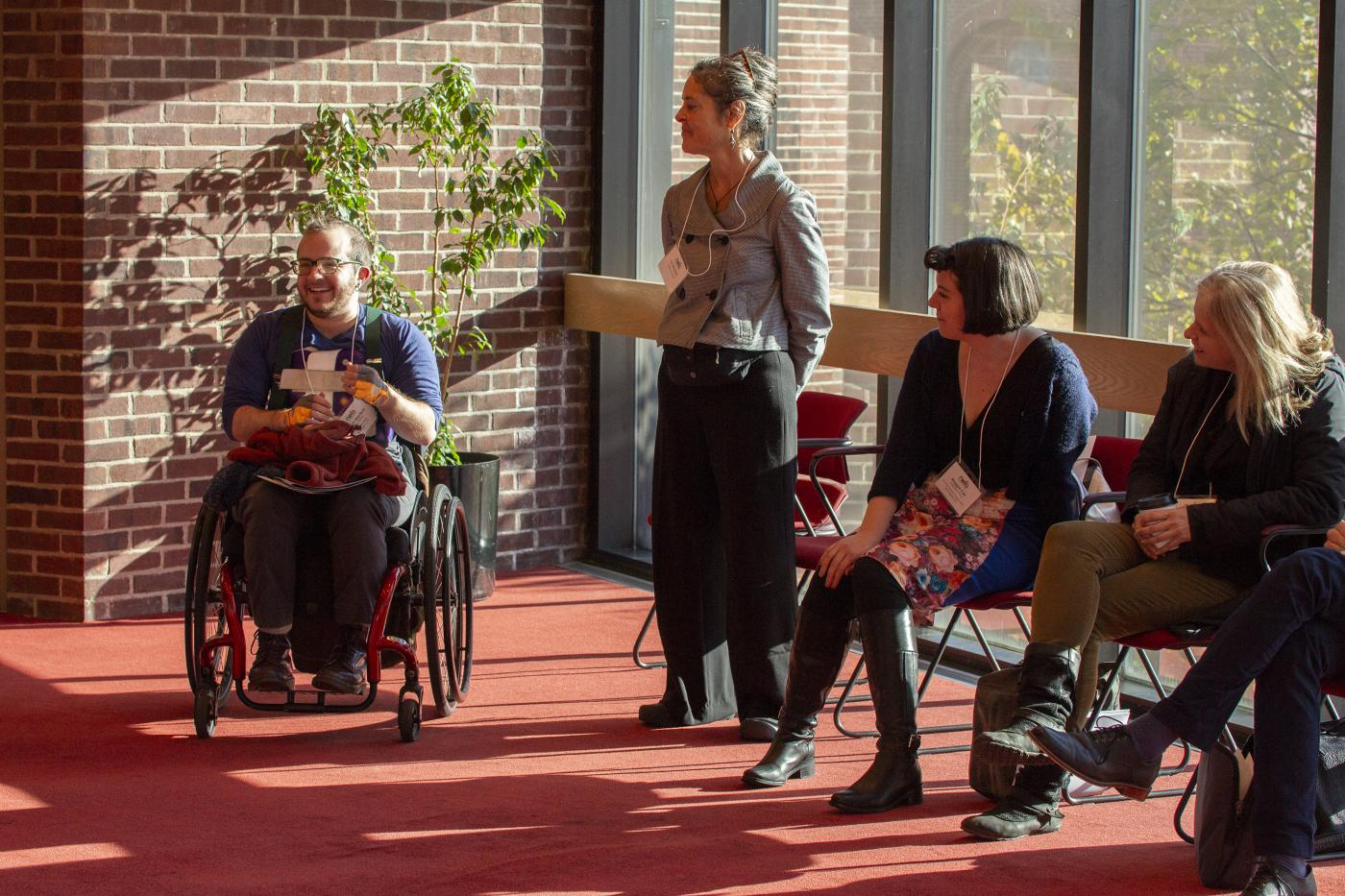 artist Toby MacNutt speaks to a group of people at the 2018 Idea Swap New to NEFA session. Toby is smiling and seated in their wheelchair next to other participants who watch them speak. Sunshine streams through tall glass windows behind the participants into the meeting room.