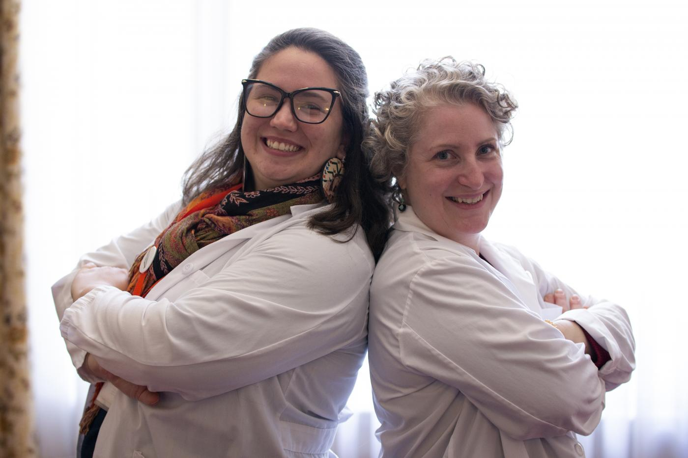 Two smiling, labcoat-wearing women pose back to back with their arms crossed