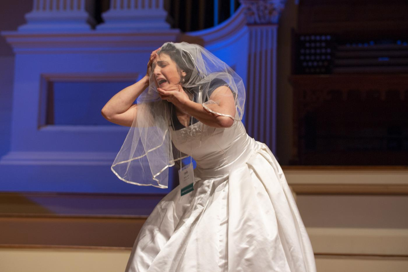 "artist Sara Juli performs an excerpt of her new work (in development) titled ""Burnt Out Wife"" at the 2018 Idea Swap on the Great Hall stage at Mechanics Hall. She wears a wedding dress over her clothes. A wedding veil covers her face and a lanyard with a name tag hangs around her neck. Sara is slightly bent forward, holding the top of her head with her right hand and holding her left hand under her chin. She appears to cry with her eyes closed and mouth open. Blue stage lighting is seen behind her on stage."
