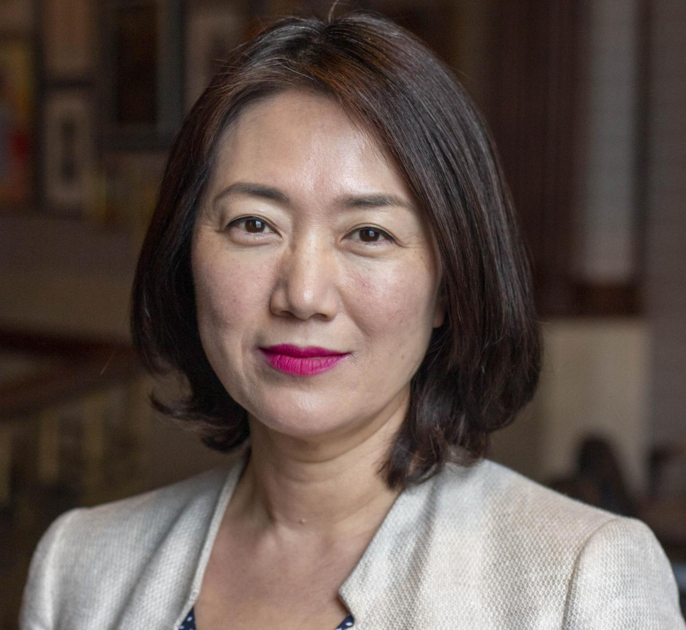 Head shot image of board member Min Jung Kim; she is smiling and wearing a ivory jacket.