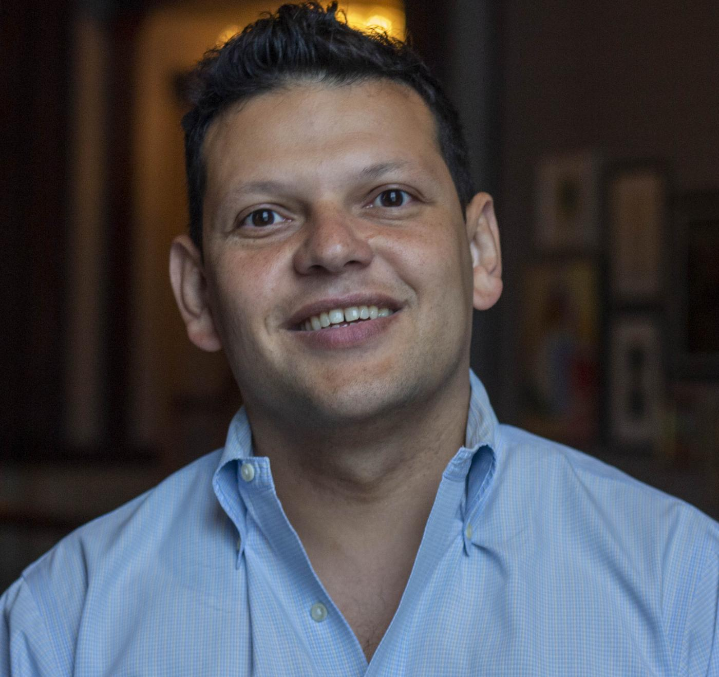 Head shot image of board member Ivan Espinoza-Madrigal; he is wearing a blue shirt and smiling.