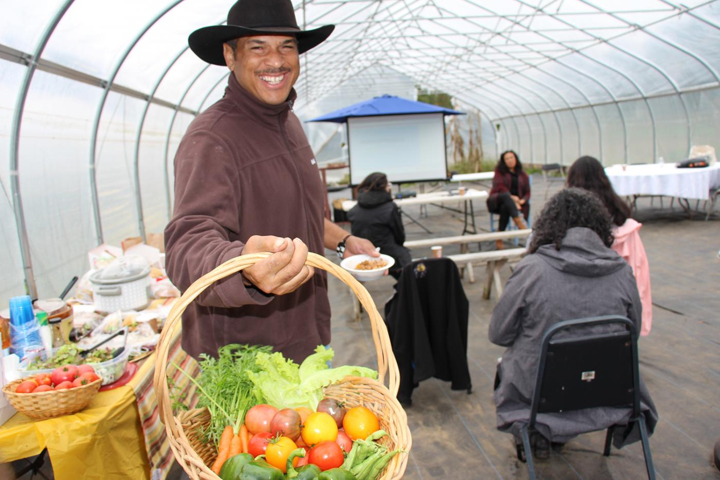 "Cassius Spears, founder of the Narragansett Food Sovereignty Initiative and caretaker of the Crandall ""minacommuck"" Farm, smiles facing the camera while holding a basket full of  freshly picked carrots, tomatoes, green beans, and peppers in a high tunnel at the Markets & Marketing workshop. A lunch buffet table is behind Cassius and workshop participants are seated in the background."