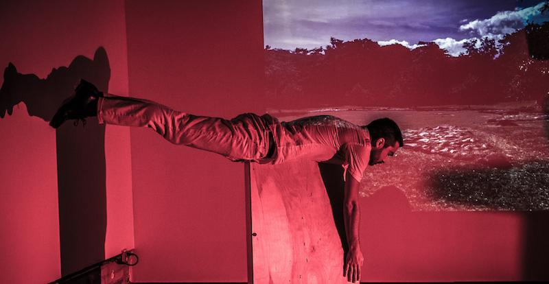 a person balances on their ribcage on a pedestal. A wash of pink light and a video projection of sky