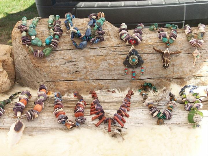 A display of a dozen necklaces made from colorful shells and natural materials displayed on driftwood.