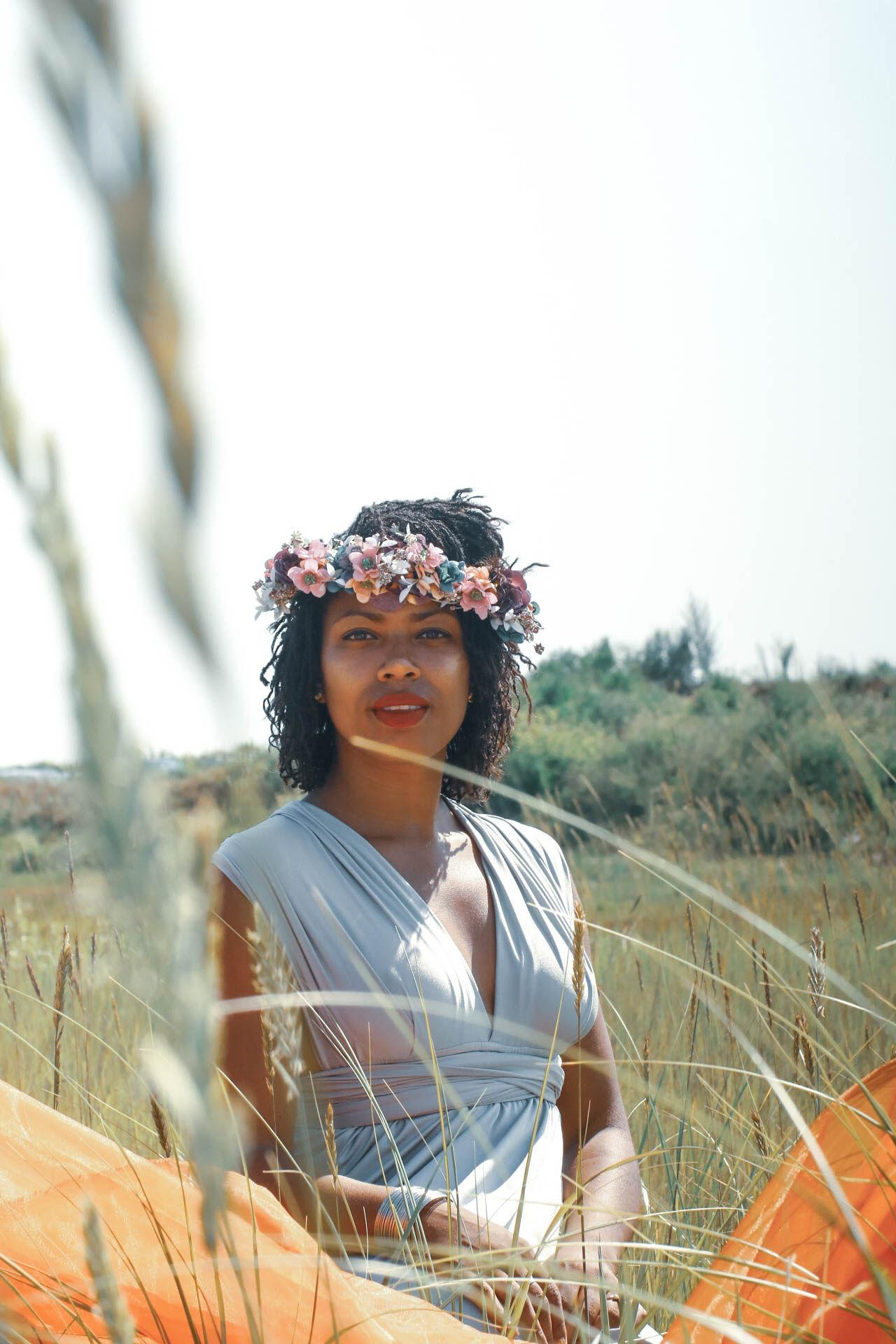 Jenny, in a floral headress, smiles behind grains that are out of focus in the foreground.