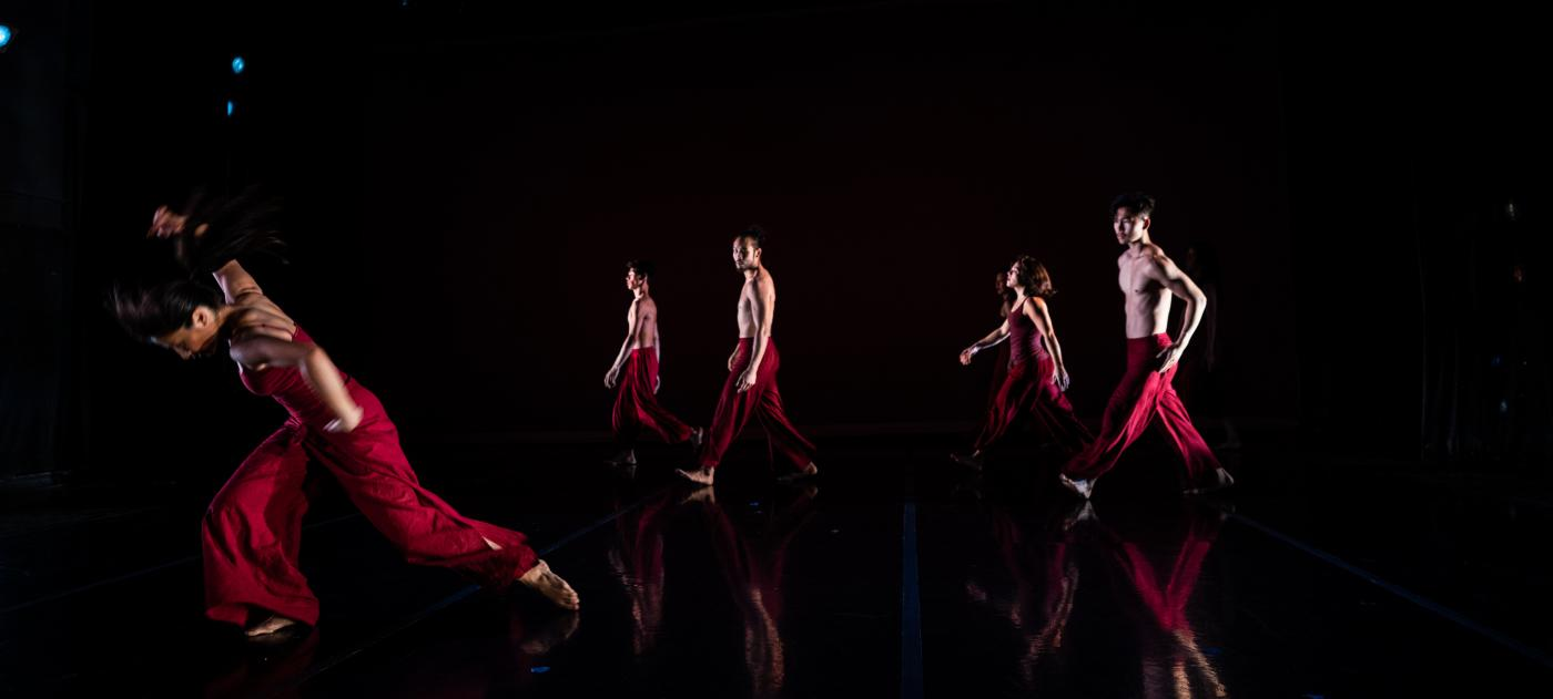 On stage, four dancers, in red outfits, walk behind an impassioned performance.