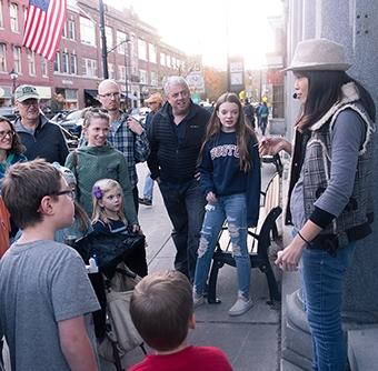 A woman wearing a fedora and a microphone speaks to a small crowd of all ages on street filled with brick buildings.