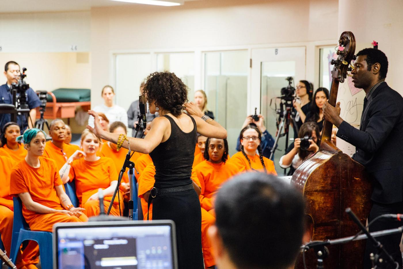 A woman and band with cello conduct a concert in front of a crowd of incarcerated women.