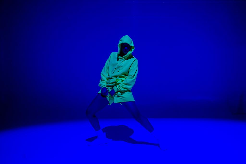 Person in a neon yellow hoodie dances in a space lit by blue light