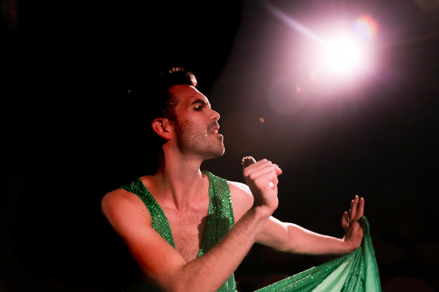 John sings into a microphone, while wearing makeup and a green dress, in front of a bright spotlight.