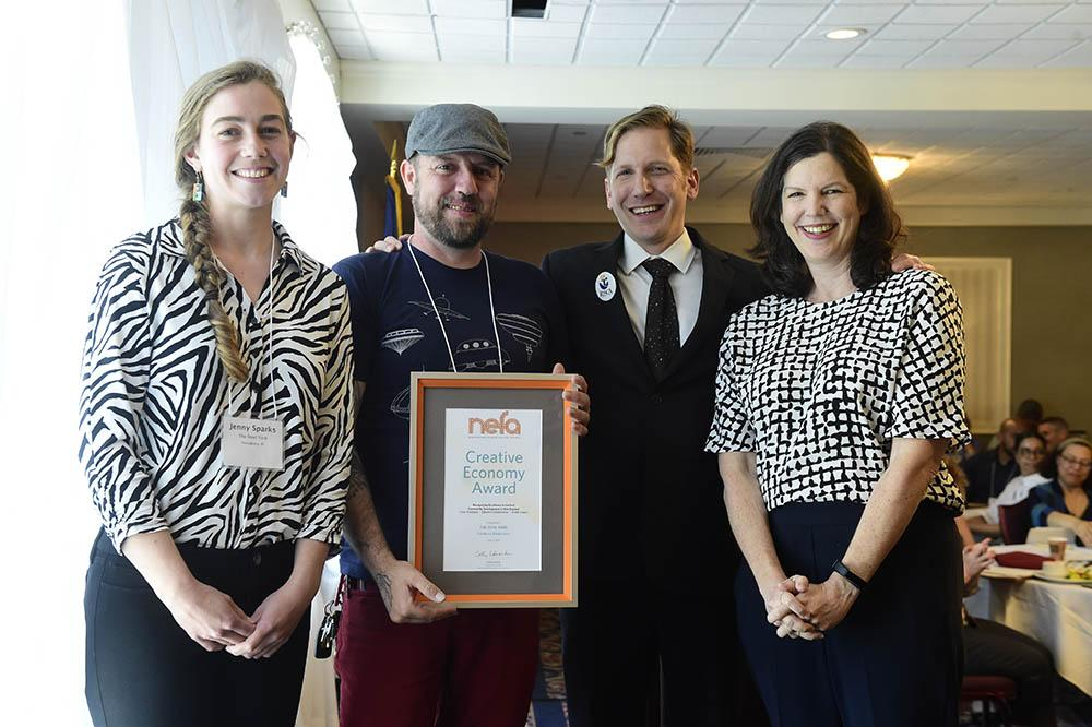 4 people stand shoulder to shoulder; one holds framed award that reads NEFA's Creative Economy Award