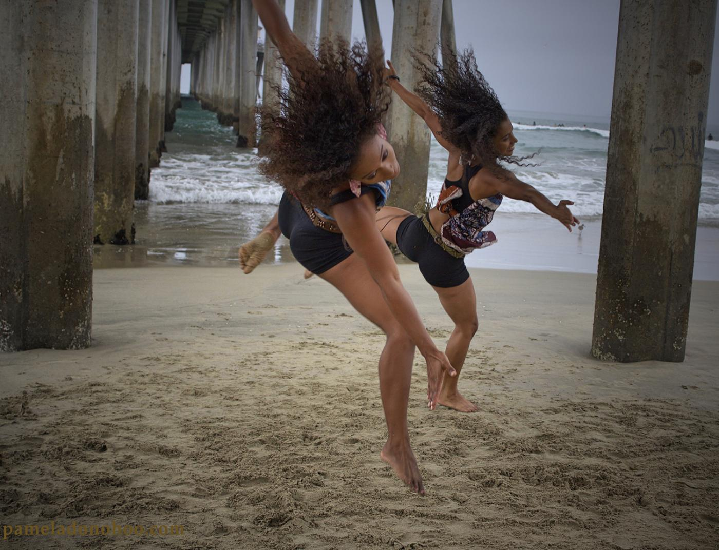 Under a dock, two blacks girls dance in the sand.