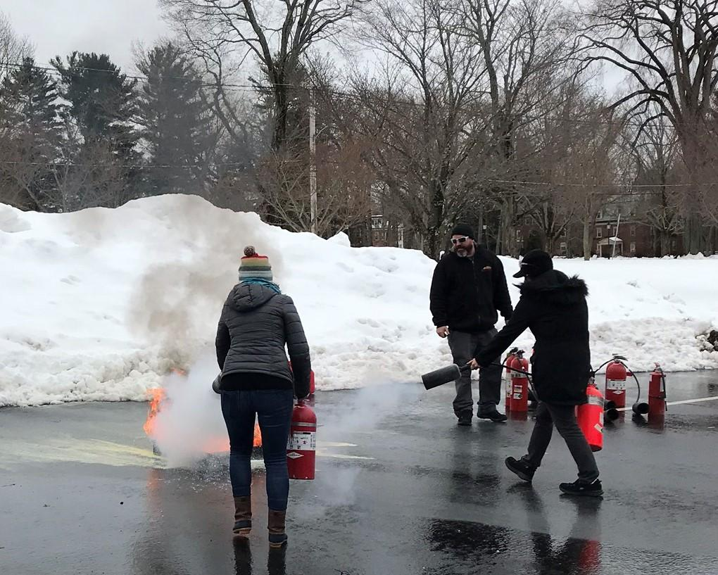 By a snowbank, two people put out a fire with extinguishers.