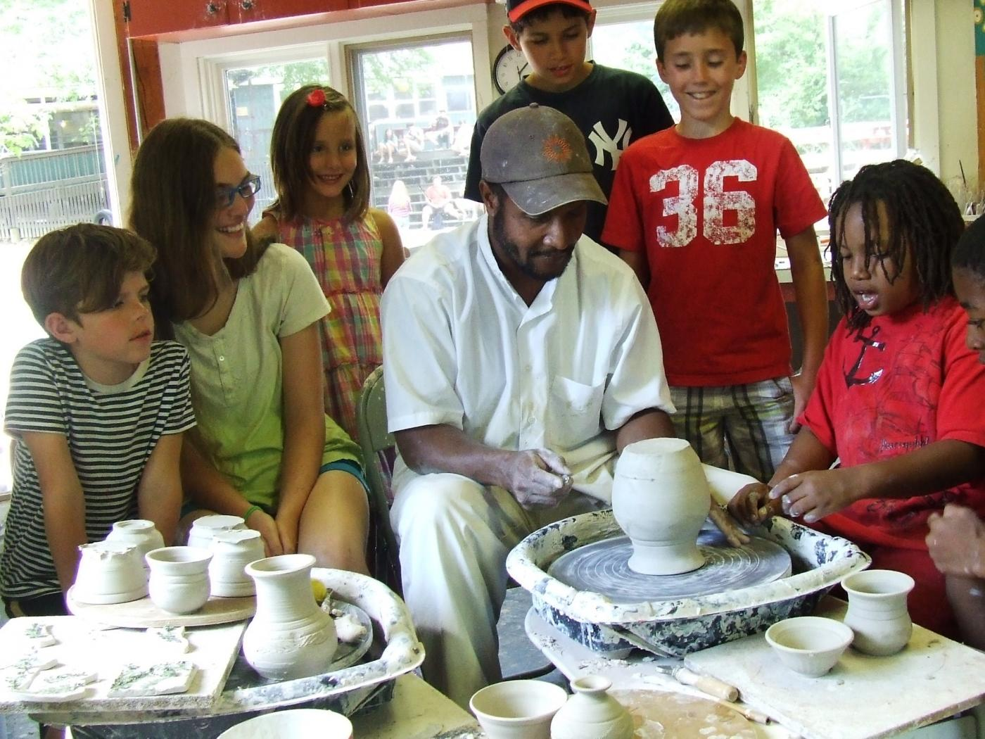 Sculptor demonstrates how to use a pottery wheel to six students
