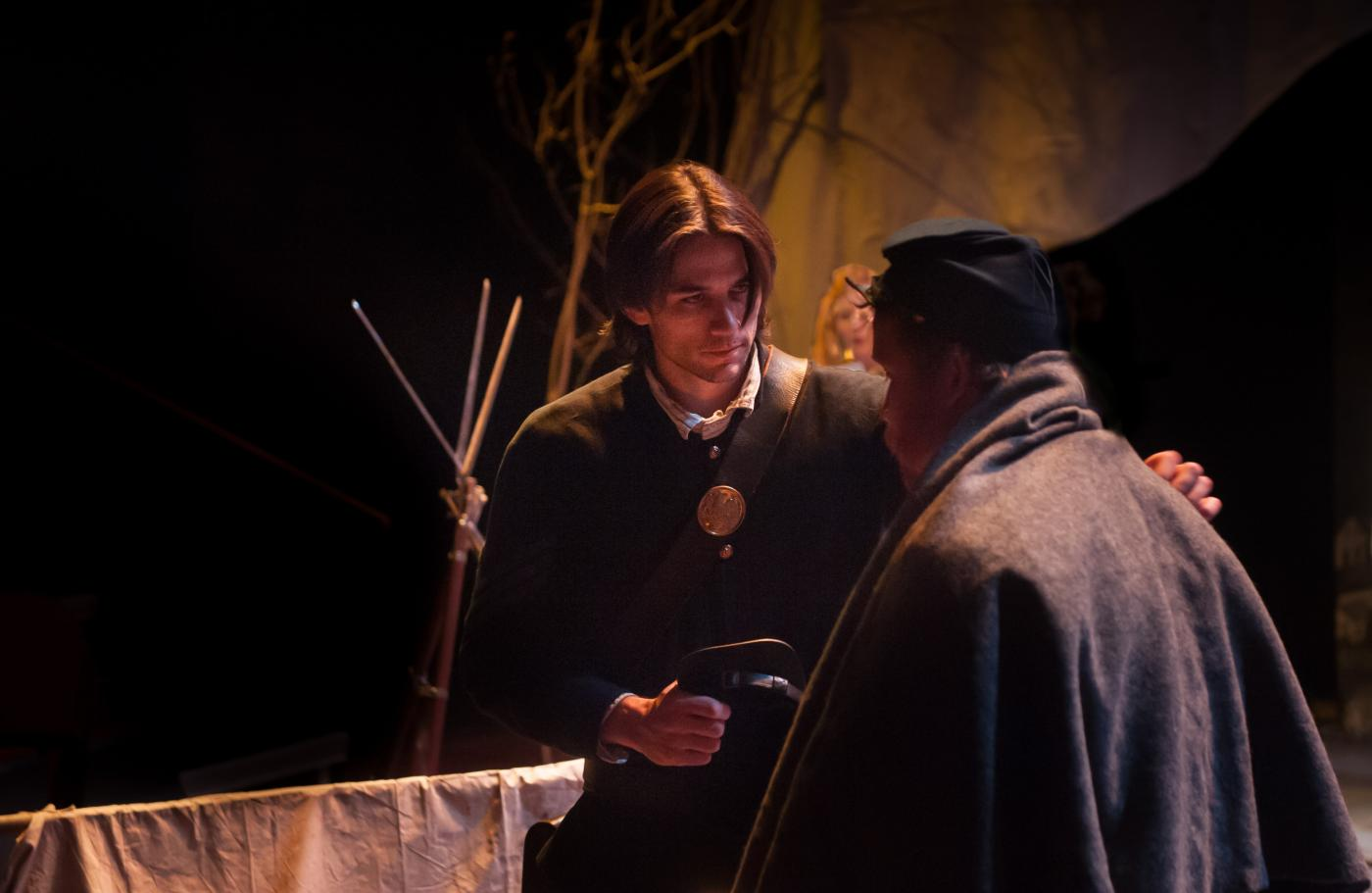Two actors in civil war era attire have a conversation on a dimly lit stage