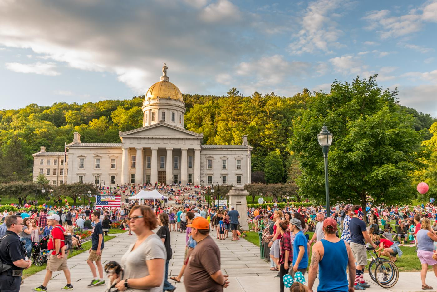 Image of a crowd of people on a warm sunny day with Vermont's capitol building in the background.