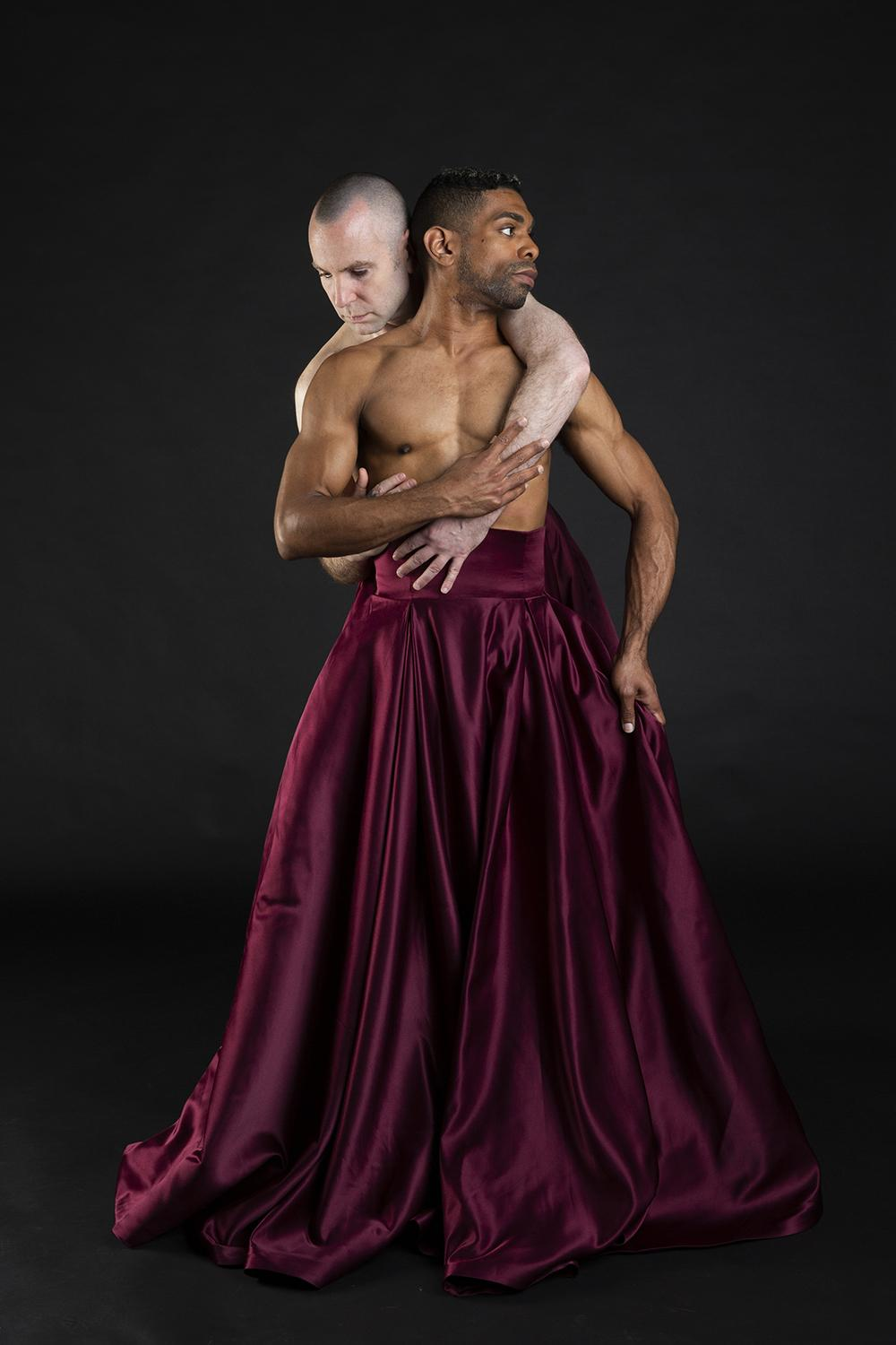 Two men caress; one of the men wears a long maroon skirt.