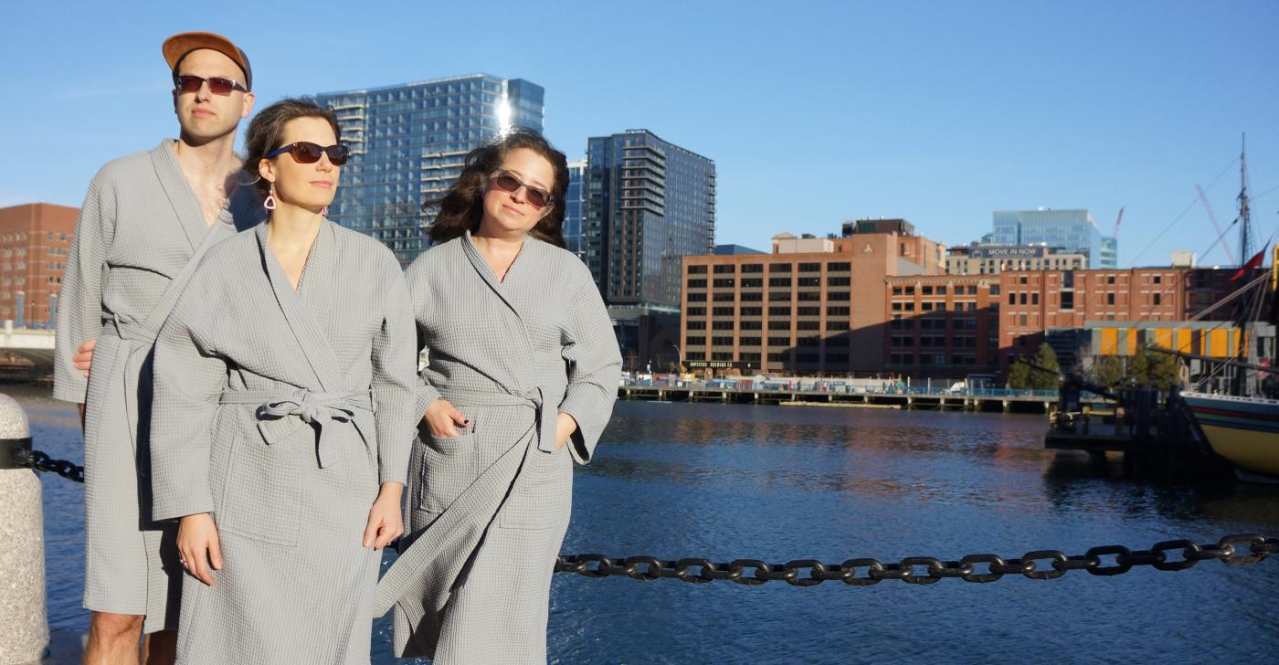 Two women and a man pose by a body of water in sunglasses and bathrobes.