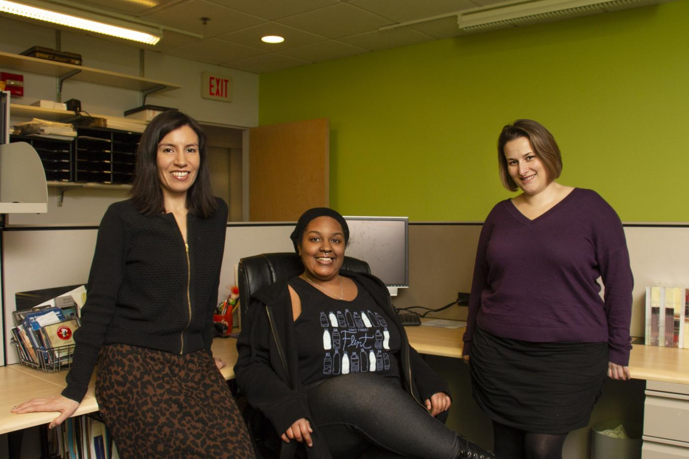 Three people pose and smile in an office cubicle.