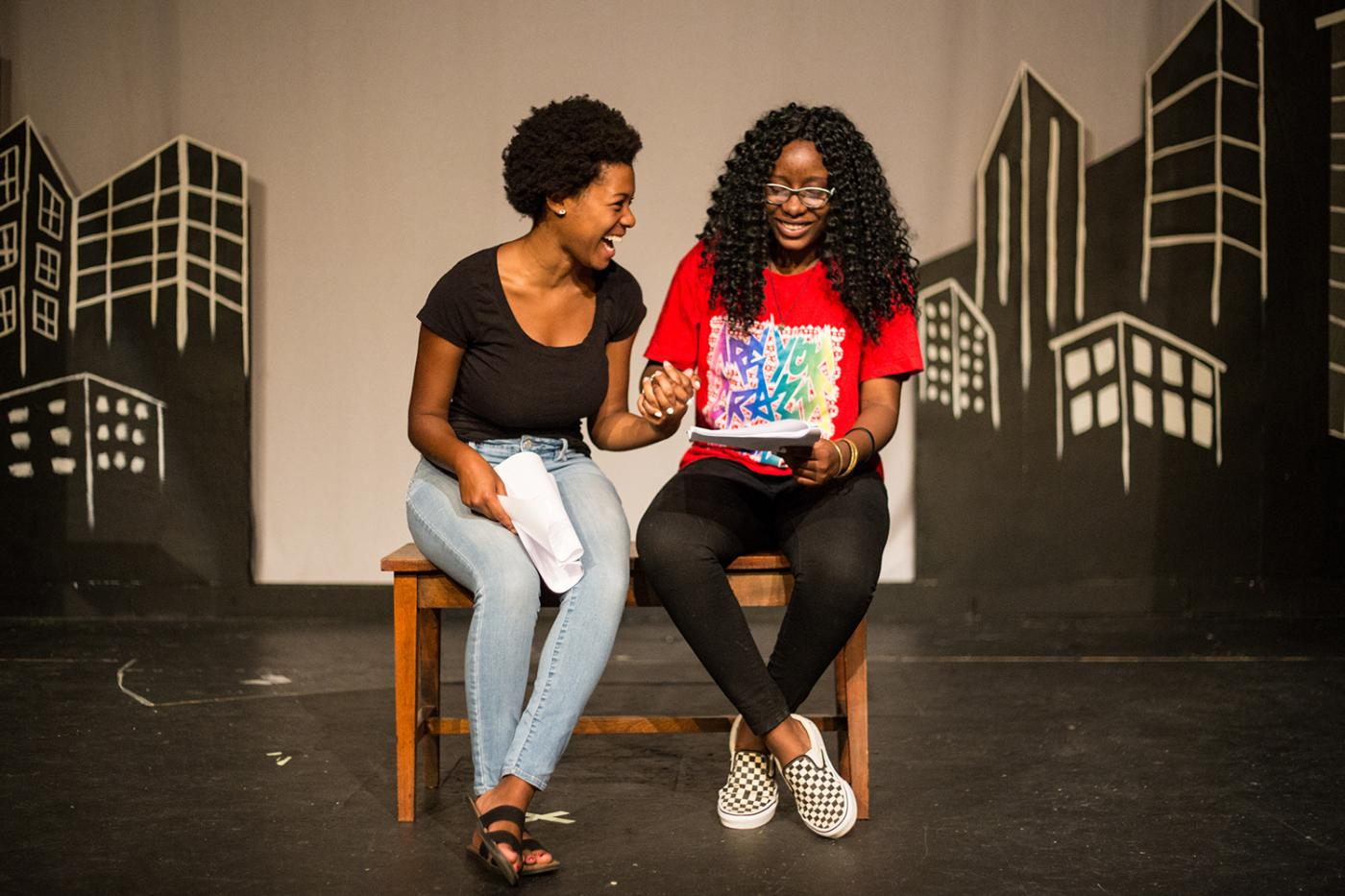 Two young women sit on a stage reading lines in front of an illustrated cityscape.