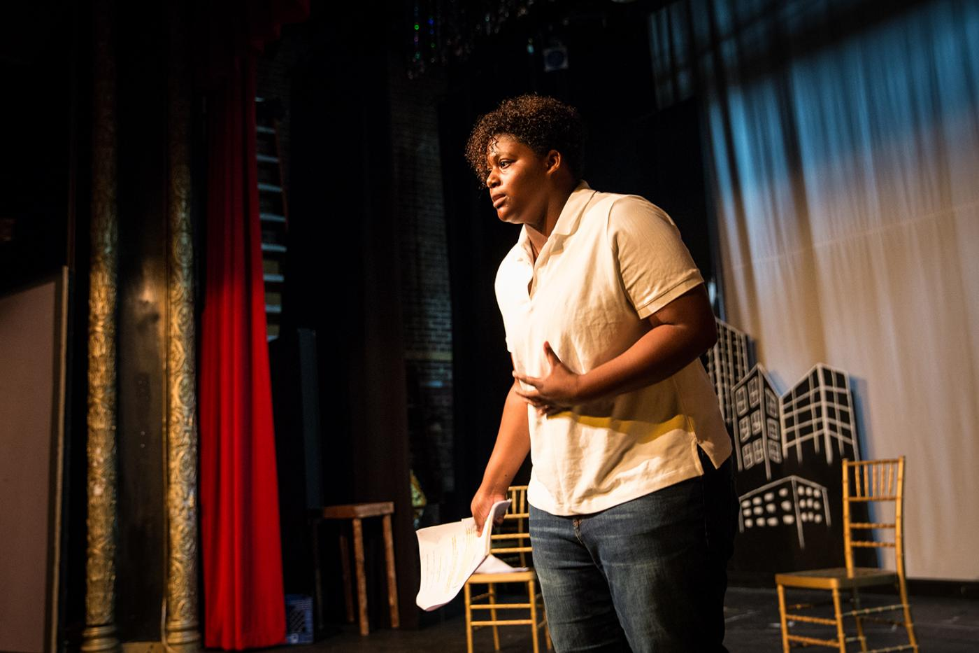 A young person delivers an impassioned speech on a stage, with their hand in a fist by their core.