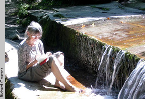A woman reads next to a short waterfall