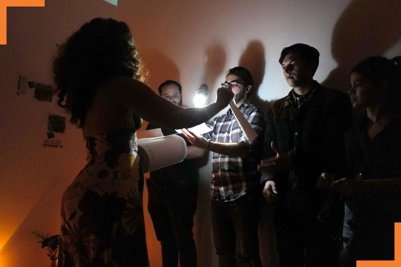 In a dark gallery space, Yara reads from a text, while an audience member holds a flashlight over the document.