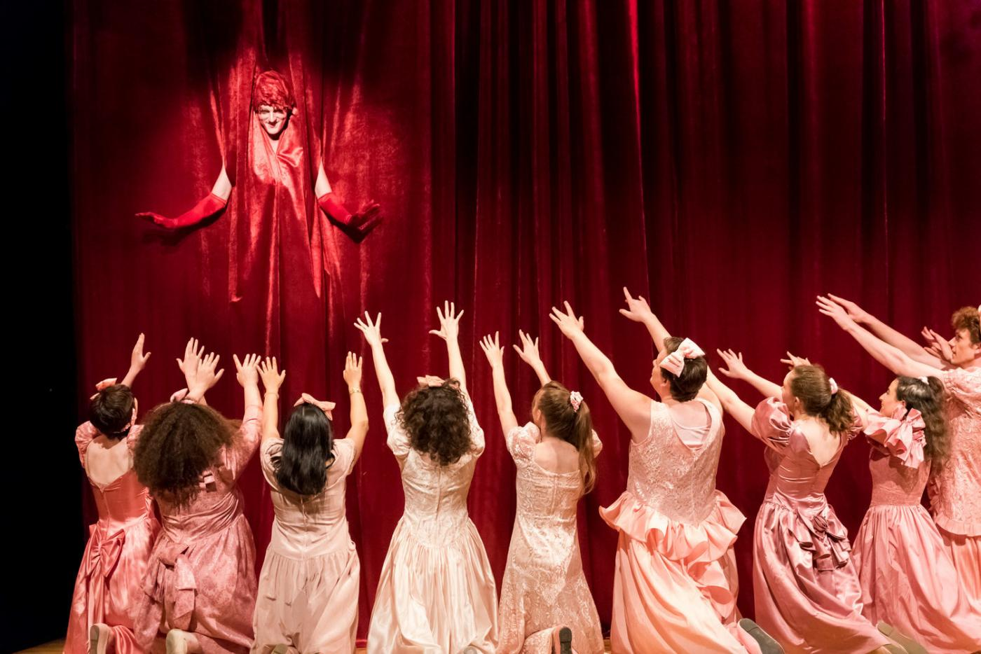 From a red curtain, a man in drag is spotlight. Before the curtain, a crowd of men and women in pink dresses hold their arms up.