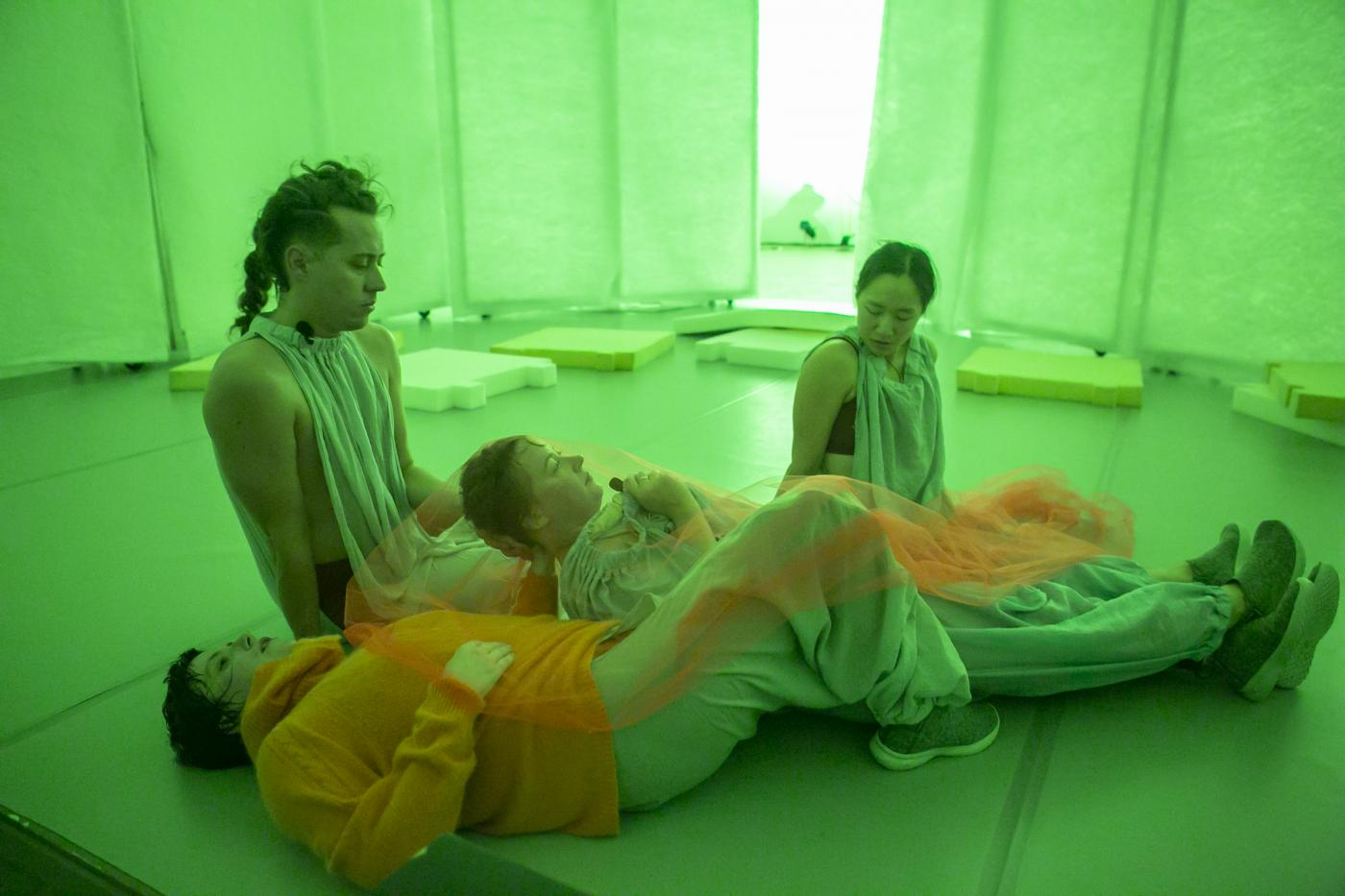 In a room lit by a neon green light, four dancers lay together.